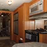 A galley style kitchen with a three sided dinette booth that also has a three sided view. At the opposite end is a double china cabinet archway to the living area. The kitchen is equipped with a deluxe overhead microwave oven, large storage pantry and double door refrigerator opposite the sink and built in dishwasher - all making this easy to run kitchen a dream.