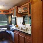 This rear three sided dinette and kitchen with a galley style work area has a double china cabinet archway at the entry from the living area. The custom built cabinetry above the sink and around the upper dinette area gives you plenty of storage. A built in dishwasher is at your fingertips.